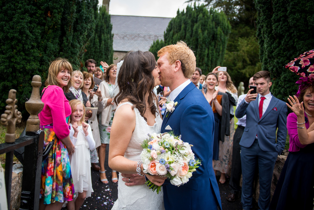 Photo of the bride and groom kissing after being showered with confetti. Location is outside the church in Llandegla.