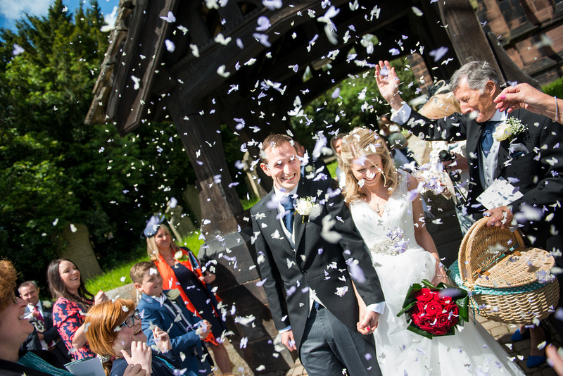 Image of the bride and groom getting showered with confetti after their wedding ceremony in Davenham.