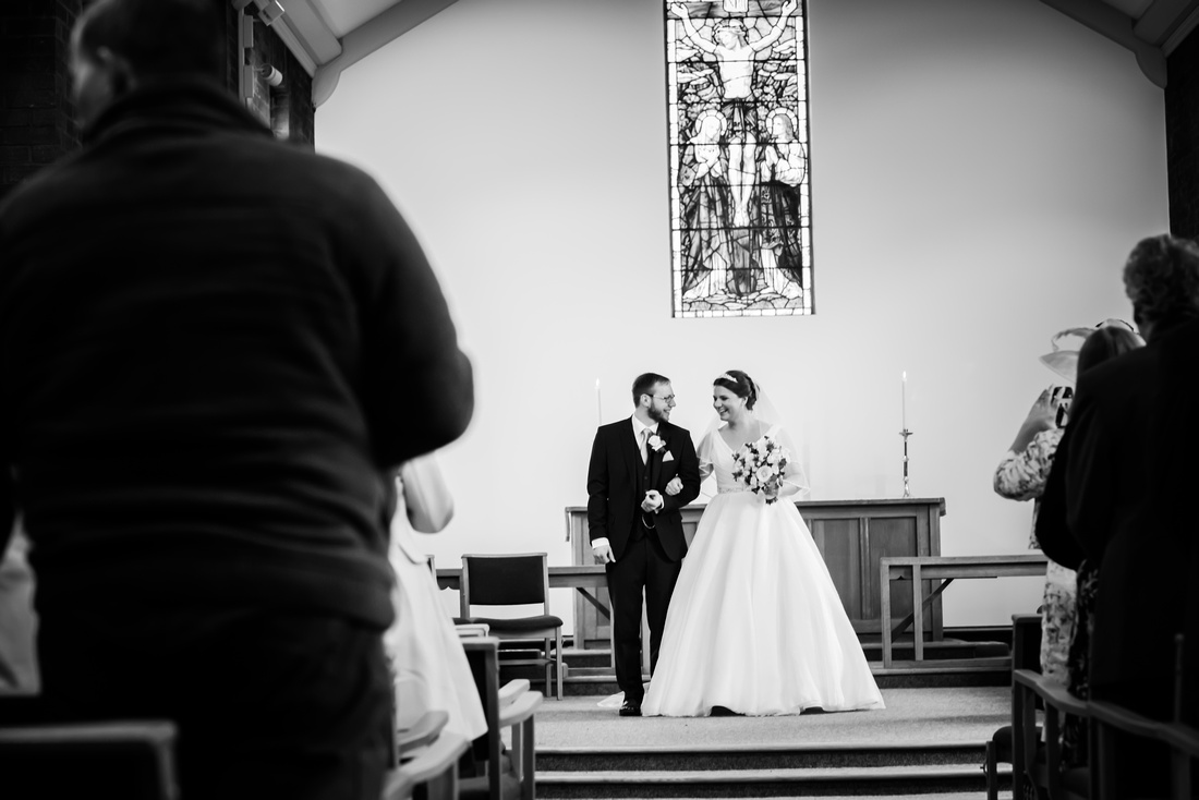 Black and white image of the bride and groom about to leave the ceremony as husband and wife.
