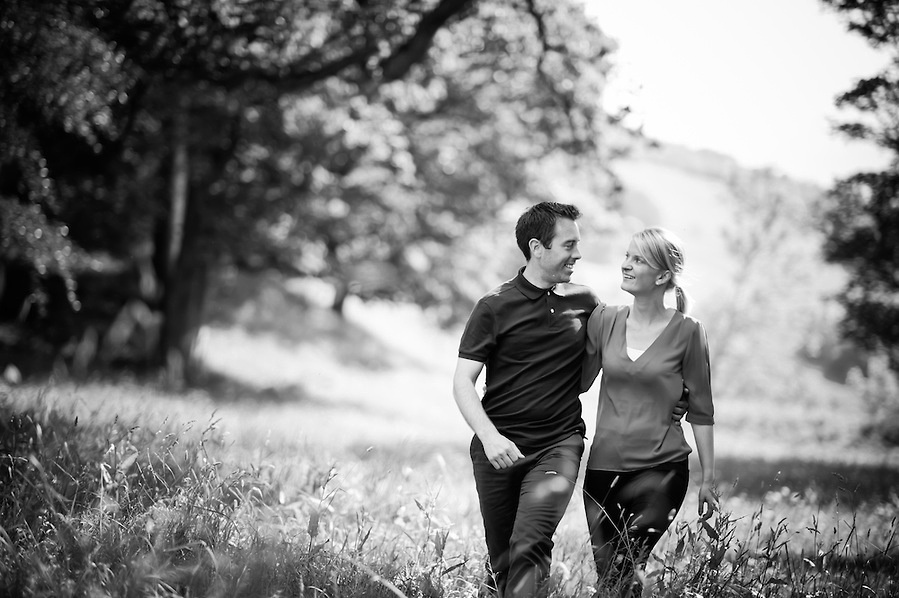 Black and white photo of an engaged couple walking during their pre-Wedding portrait session with Celynnen Photography at the beautiful Crogen Estate
