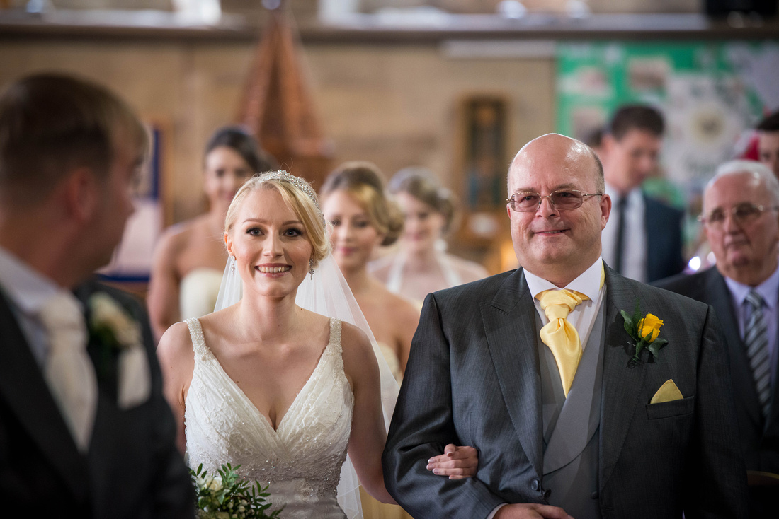 Image of the bride and her father walking down the aisle towards her groom.