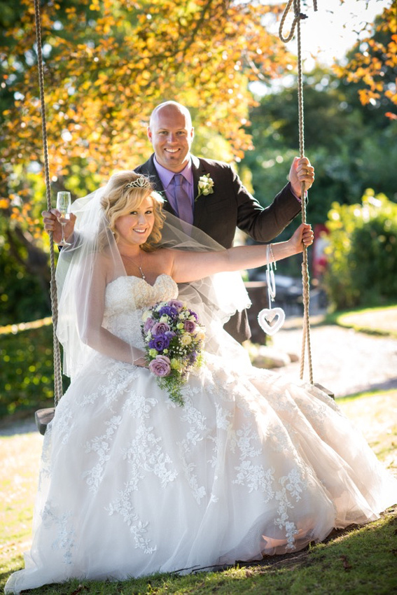 Portrait of the bride and groom on a swing at Chateau Rhianfa.