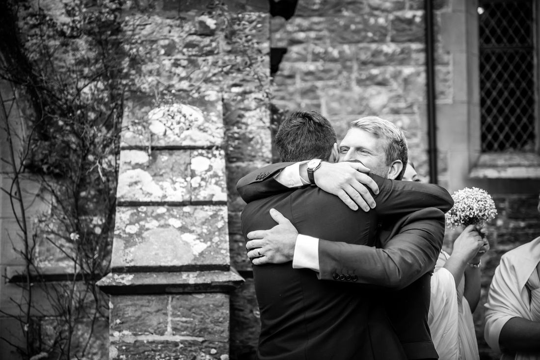 Black and white image of people congratulating the groom after the wedding ceremony in a church in Llandegla.