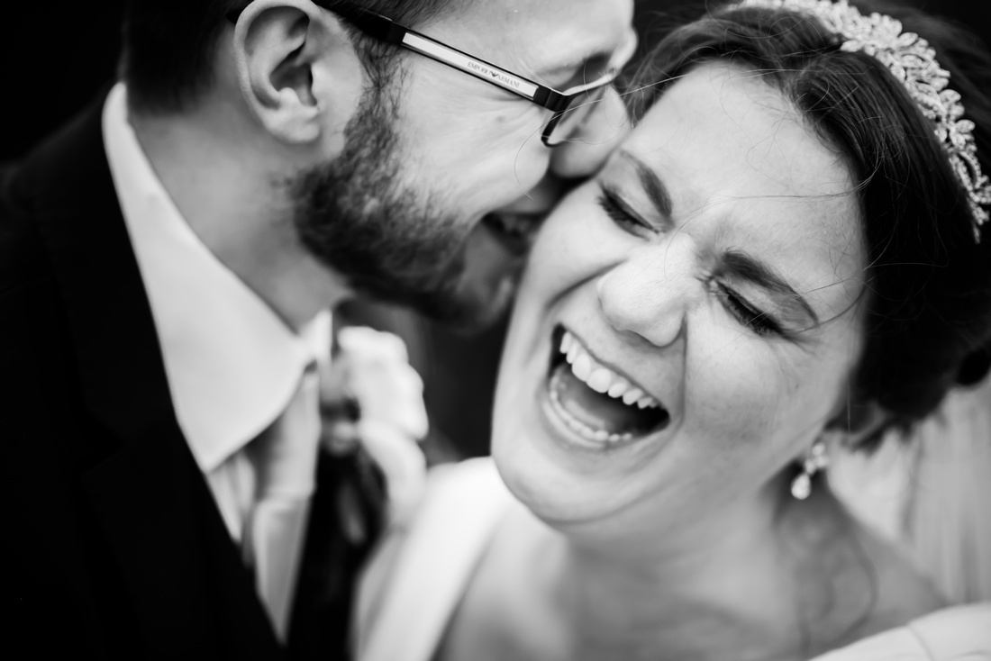 Black and white image of the bride and groom laughing together at a wedding at Mere Brook House.