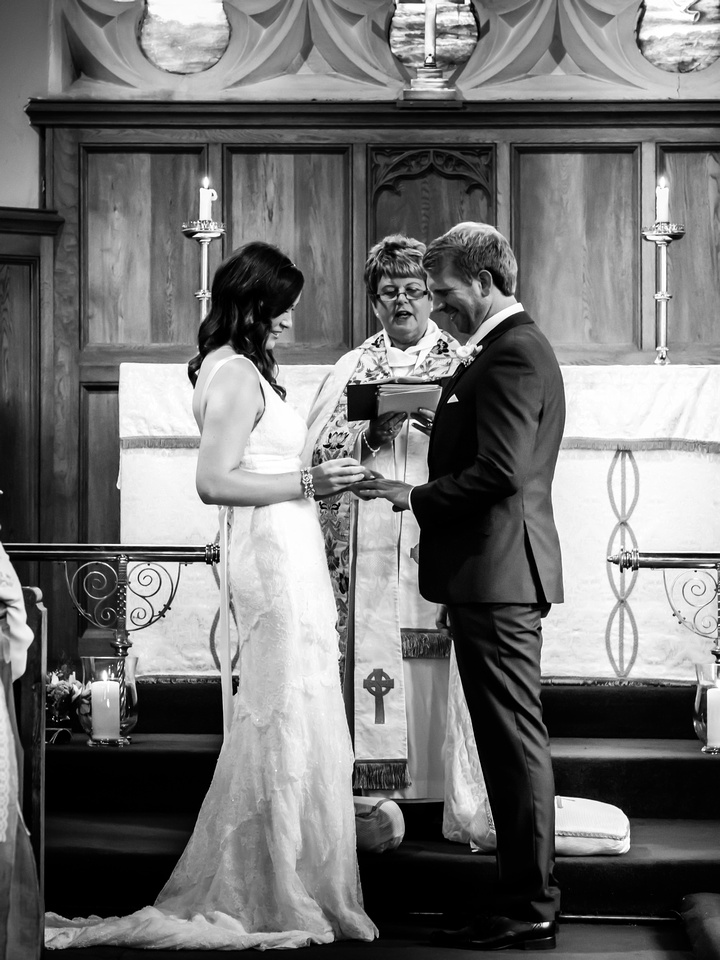 Black and white image of the bride and groom exchanging the rings during their ceremony at a church in Llandegla.