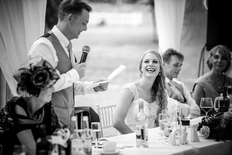 Black and white image of the bride laughing during the groom's speech at Bodrhyddan Hall.