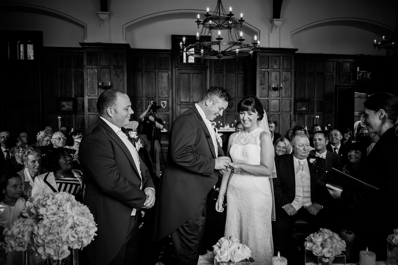 Black and white image of exchanging the rings in a wedding in Chateaux Rhianfa, Anglesey. Wedding Photographer, Celynnen Photography