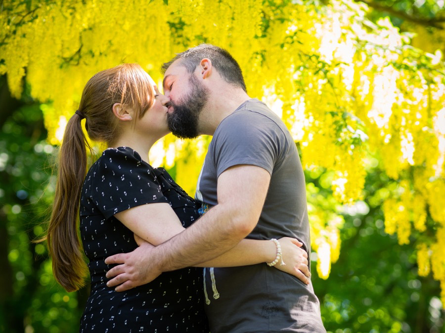 Colour photograph of Claire & Paul kissing with lovely yellow tree in the background, Sefton Park, Liverpool.