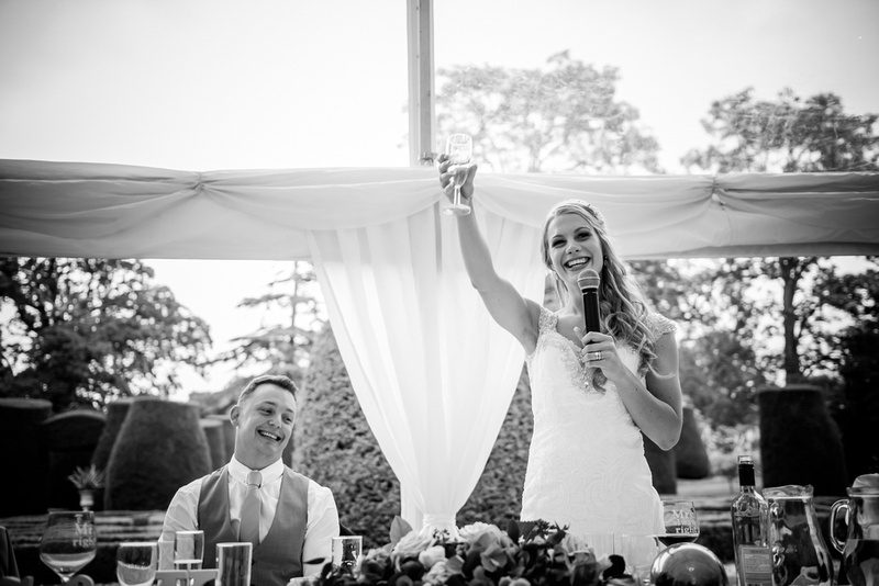 Black and white image of the bride raising a glass at her wedding at Bodrhyddan Hall.