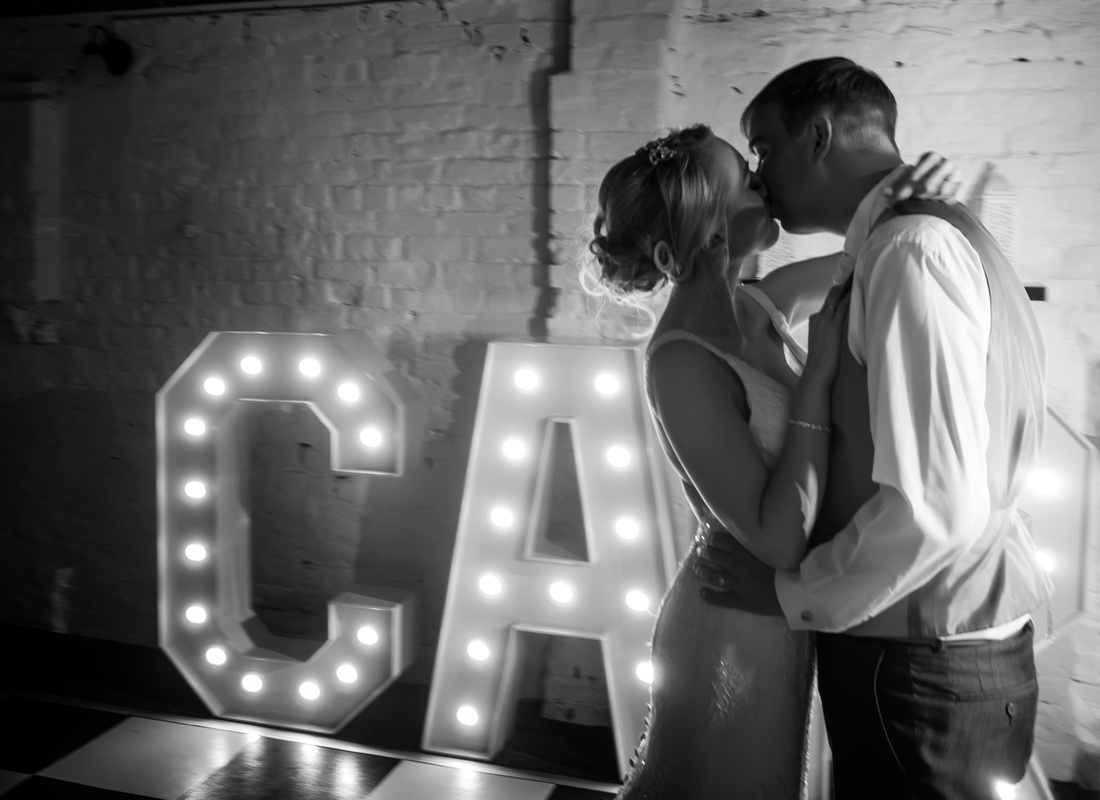 Black and white image of the bride and groom sharing a kiss on the dance floor at their wedding at Pentre Mawr.
