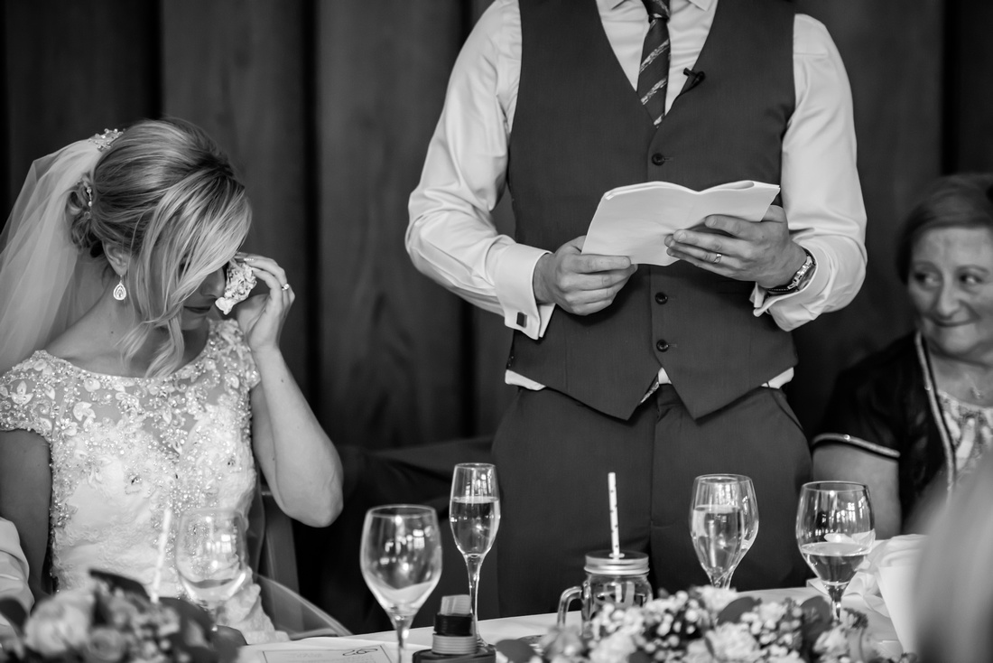 Black and white image of the bride getting emotional during the groom's speech at a wedding in Portmeirion.