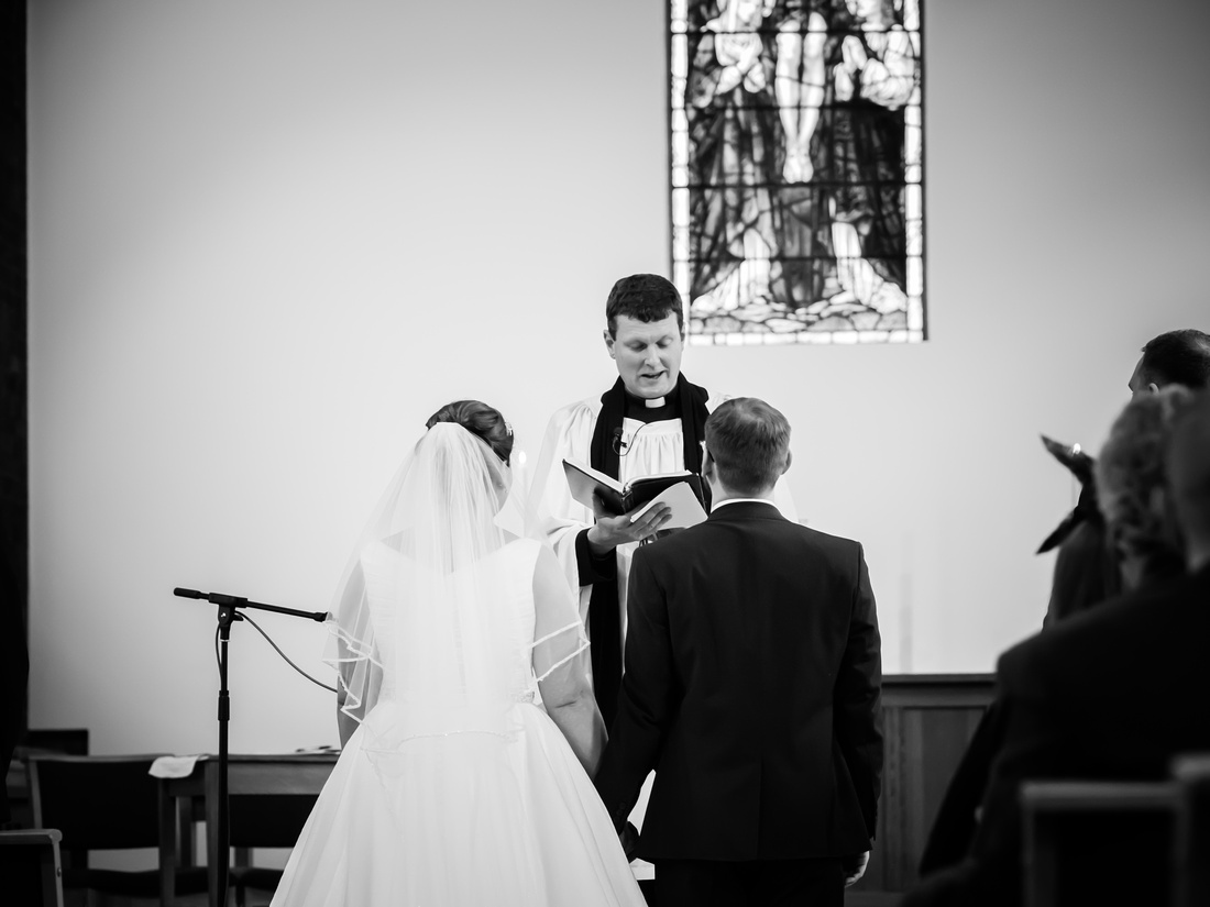 Black and white image of the back of the bride and groom during the wedding ceremony.