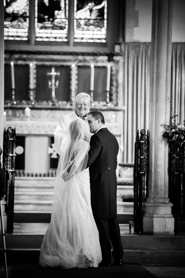 Black and white image of the bride and groom sharing a kiss in a church in Buckinghamshire