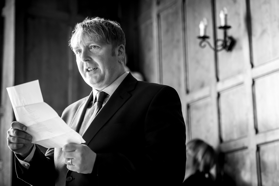 Black and white picture of a guest reading something during the wedding ceremony at Chateau Rhianfa.