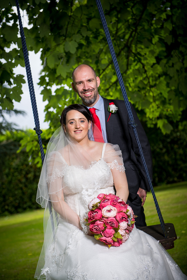 Image of the married couple sitting on a swing in the grounds of Soughton Hall.