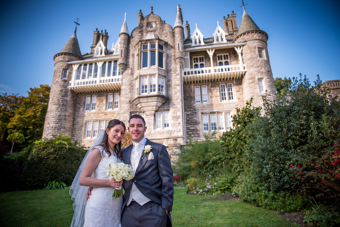Portrait of bride and groom with Chateau Rhianfa in the background.