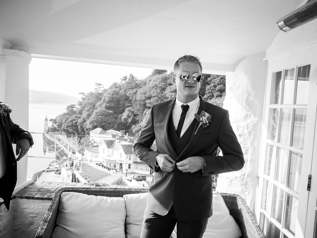 Black and white image of one of the ushers getting ready for the wedding day in sunny Portmeirion.