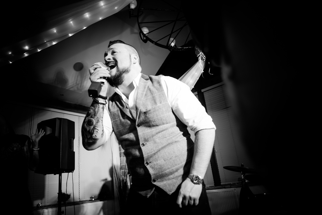 Black and white image of the singer from the band performing at a wedding at Beeston Manor in Lancashire.