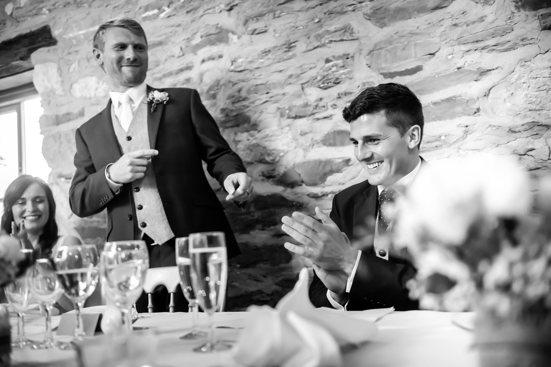 Black and white image of the groom interacting with the best man during his speech at a wedding at Plas Isaf.