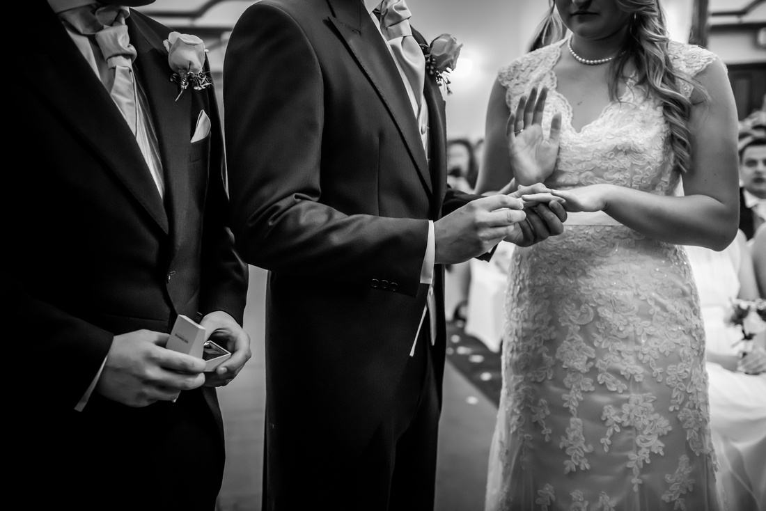 Black and white photograph of exchanging the rings during the wedding ceremony at The Kinmel.