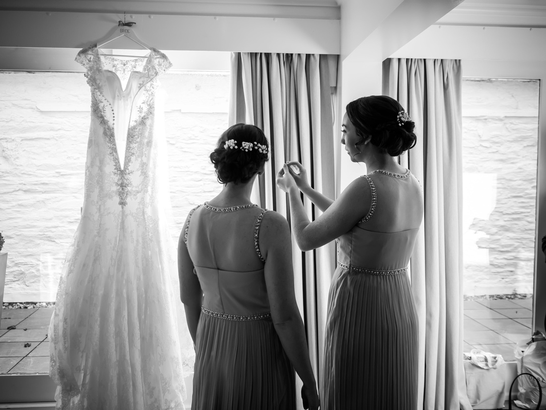 Black and white image of the bridesmaids admiring the bride's wedding dress at a wedding in Portmeirion.