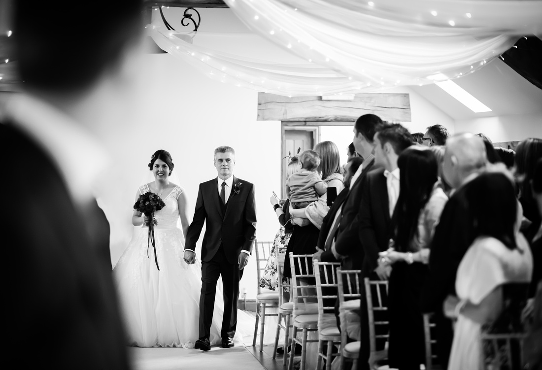 Black and white image of the bride walking down the aisle with her father at a wedding at Beeston Manor.