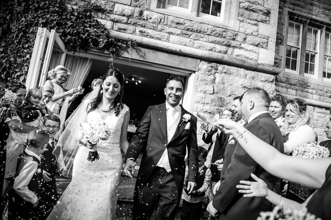 Black and white image of bride and groom getting covered with confetti at their wedding at Chateau Rhianfa.
