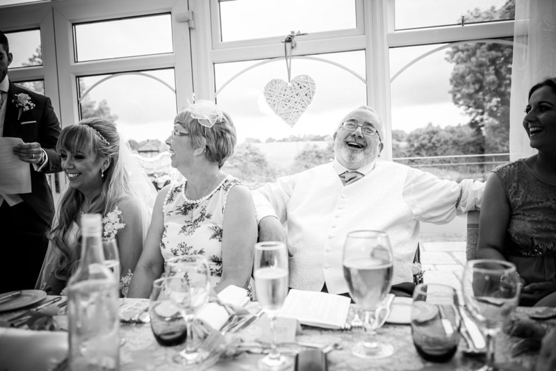 Black and white image of the father of the bride laughing during the groom's speech at The Lion Quays.