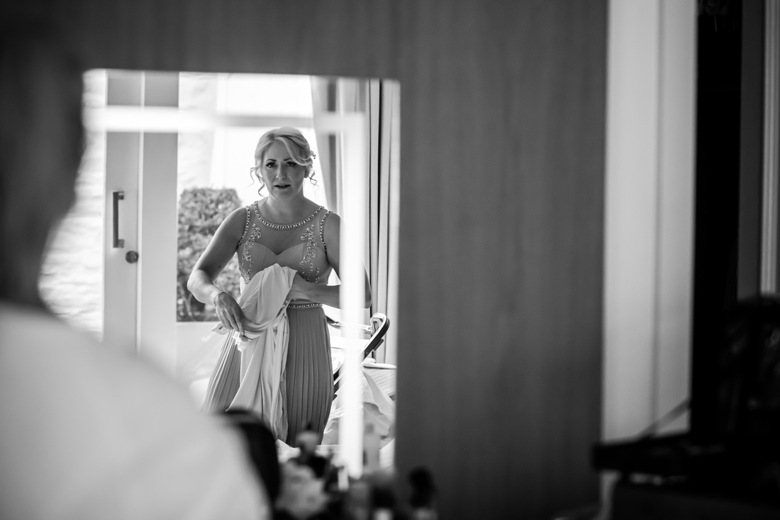 Black and white image of one of the bridesmaids getting ready for the wedding day at Portmeirion.