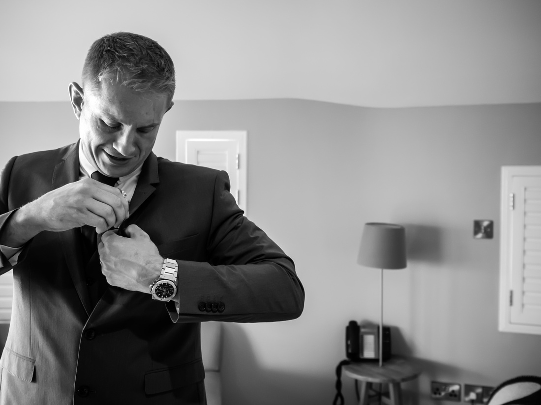 Black and white image of one of the ushers getting ready for the wedding day at Portmeirion.