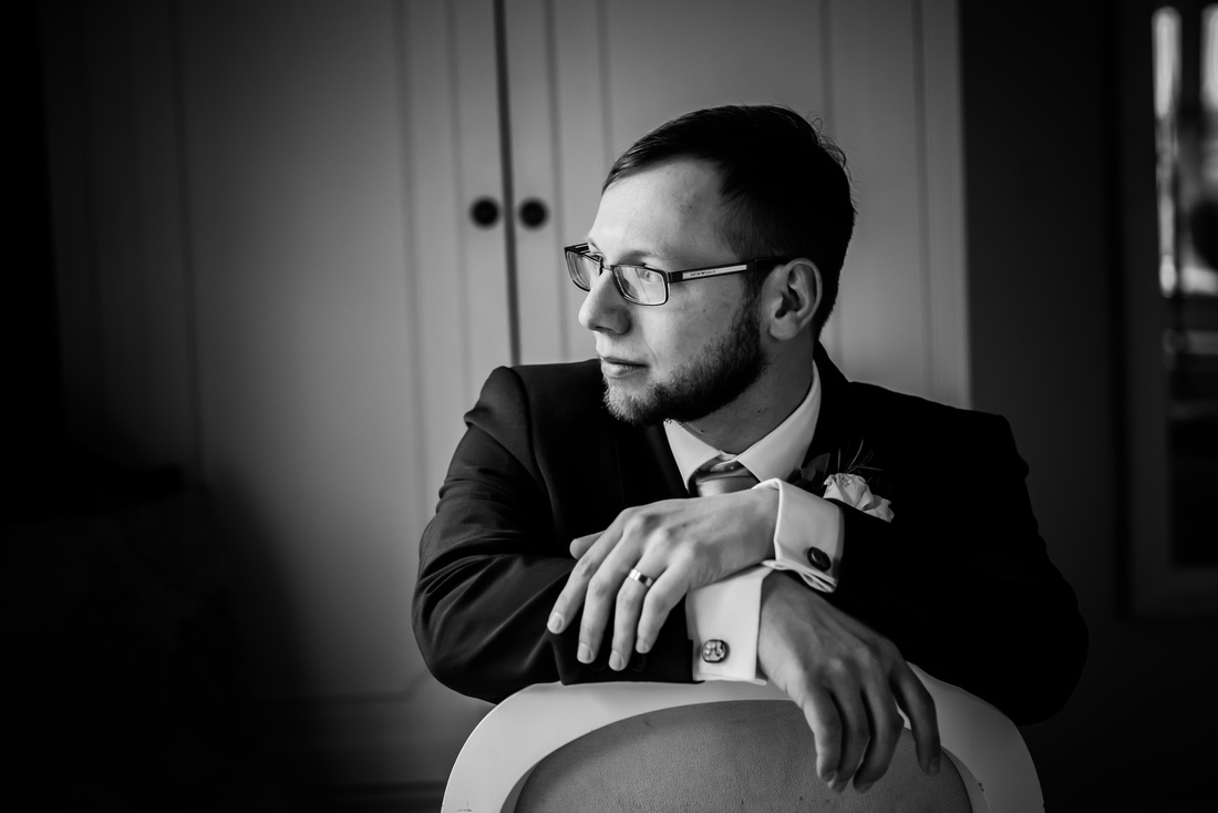 Black and white image of the groom sitting and looking at of the window at a wedding at Mere Brook House.
