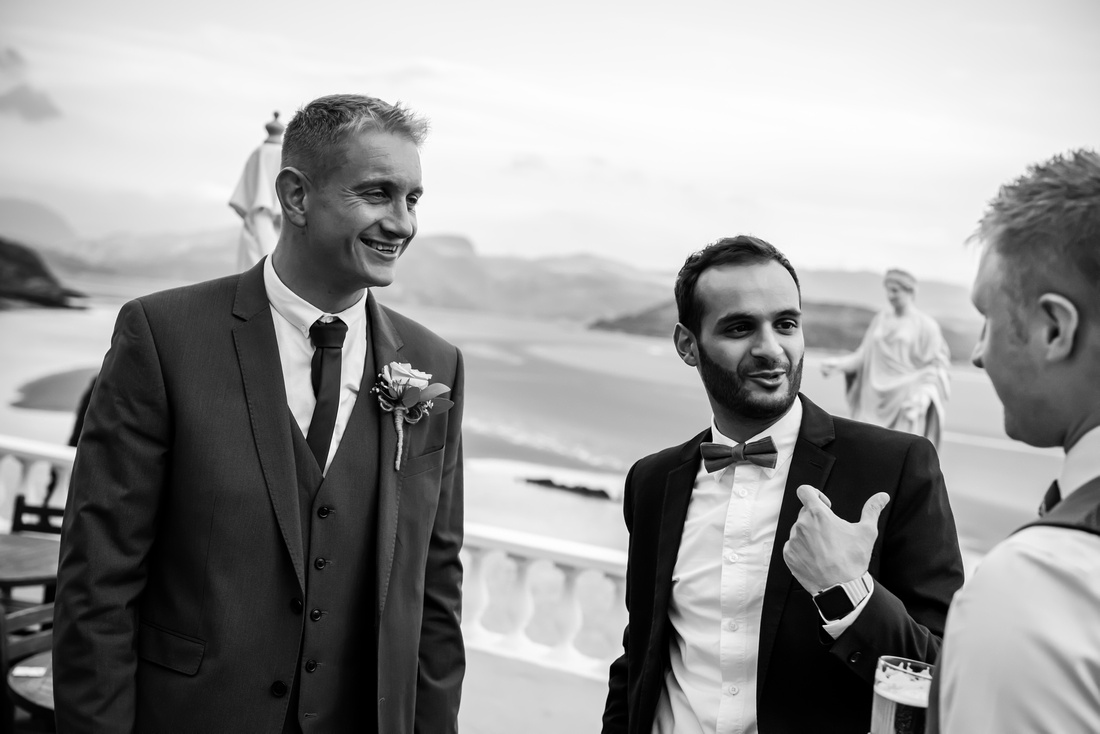 Black and white image of guests chatting at a wedding in Portmeirion.