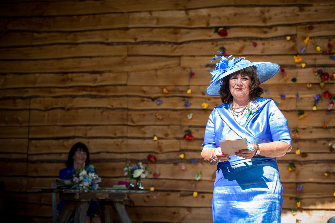 Image of the mother of the bride doing a reading during the wedding ceremony at Tower Hill Barns.
