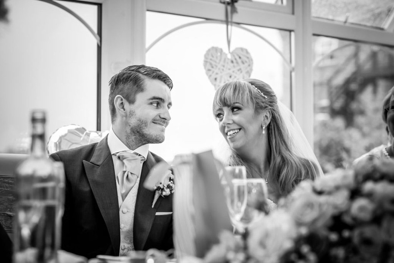 Black and white image of the bride and groom looking at each other during the speeches at their wedding at The Lion Quays.