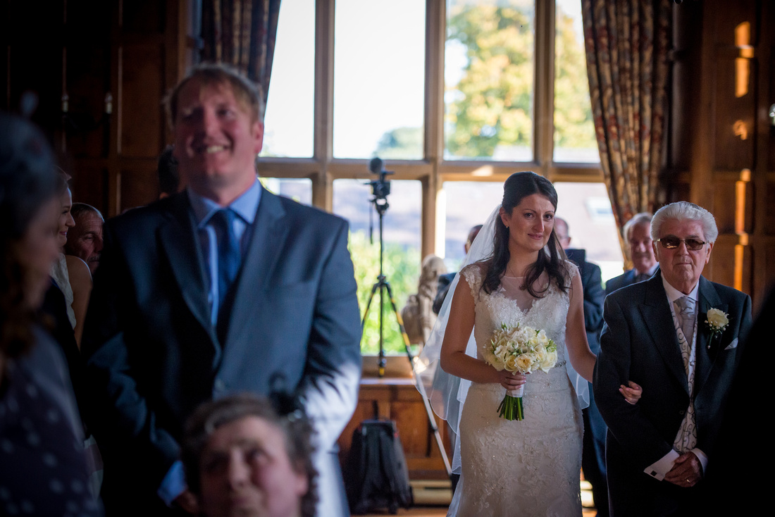 Photo of the bride walking down the isle with her father at a wedding at Chateau Rhianfa.
