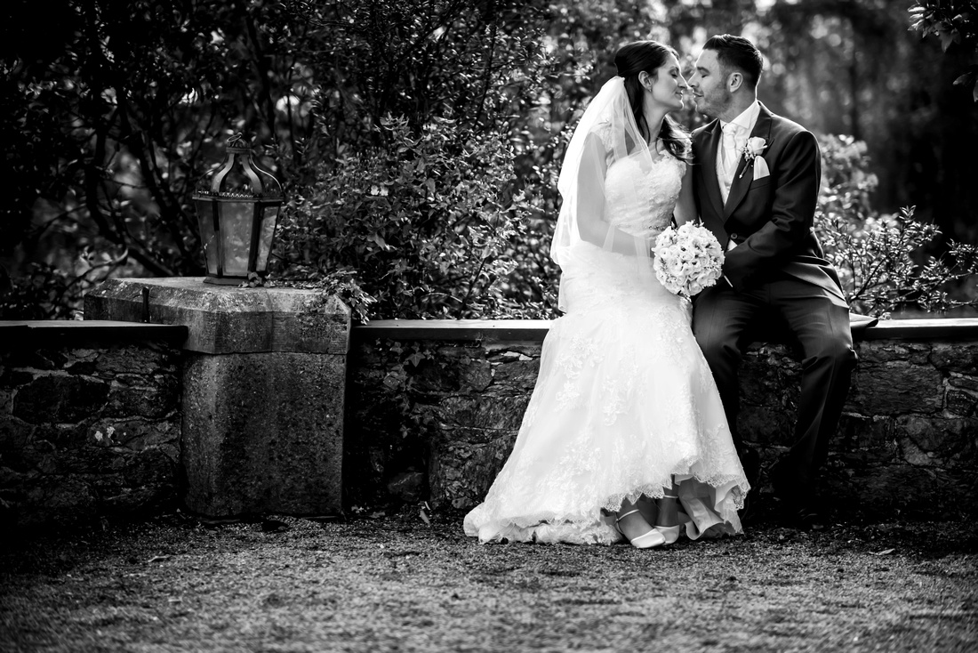 Black and white photo of the bride and groom about to share a kiss on their wedding day at Chateau Rhianfa.