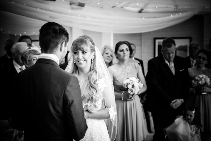 The bride looking at the groom on their wedding day at the Lion Quays in the conservatory.