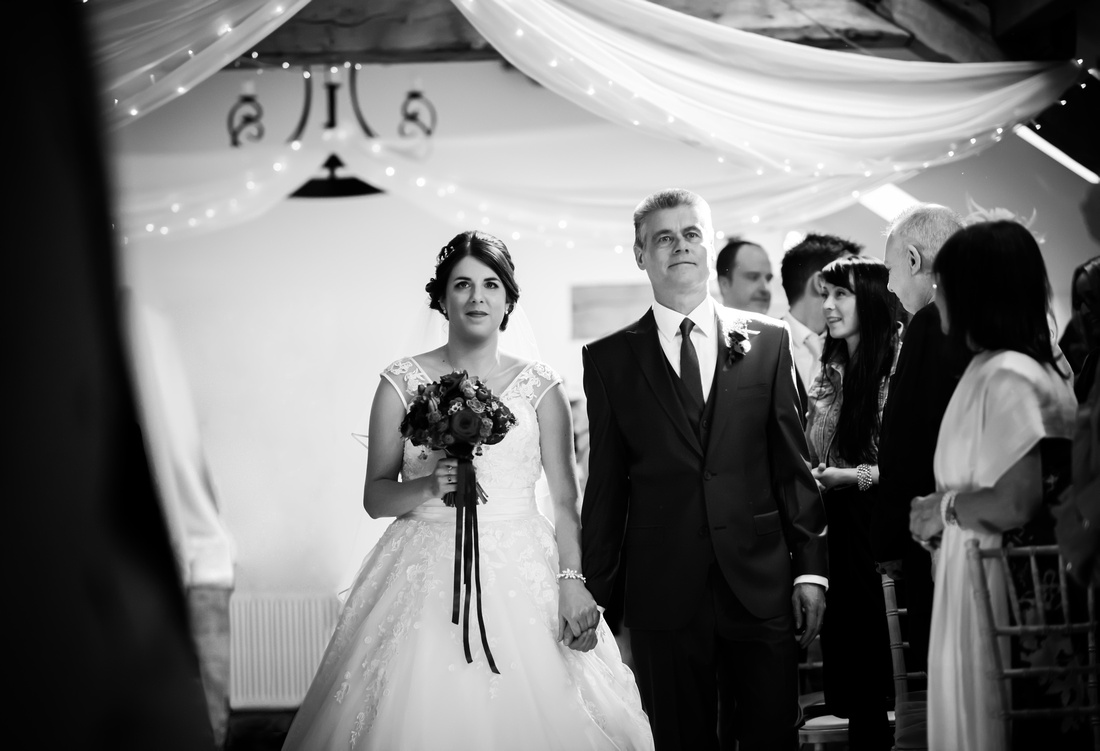 Black and white image of the bride walking down the aisle to her groom at a wedding in Lancashire at Beeston Manor.
