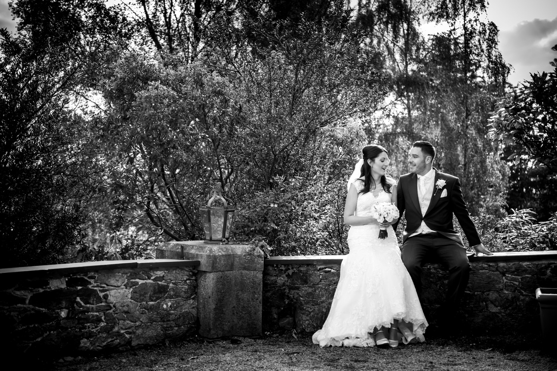 Black and white photo of the bride and groom outside their wedding venue at Chateau Rhianfa.