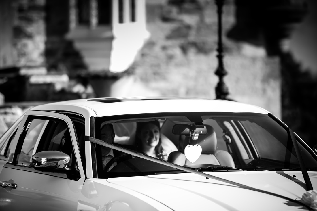 Black and white image of the bride arriving at Chateau Rhianfa.