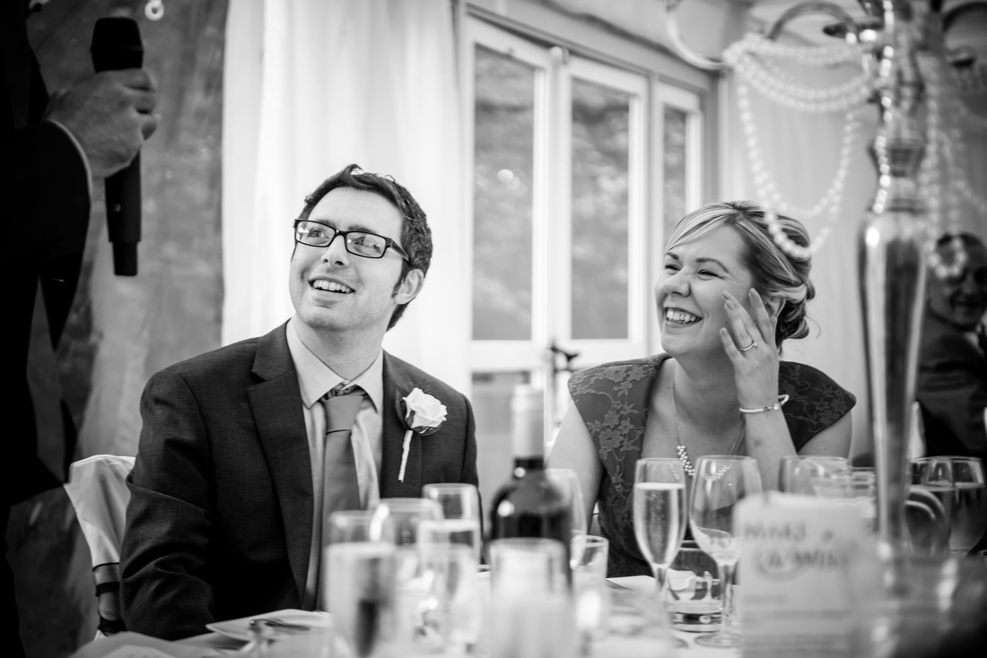 Black and white image of guests enjoying the speeches at a wedding at Soughton Hall.