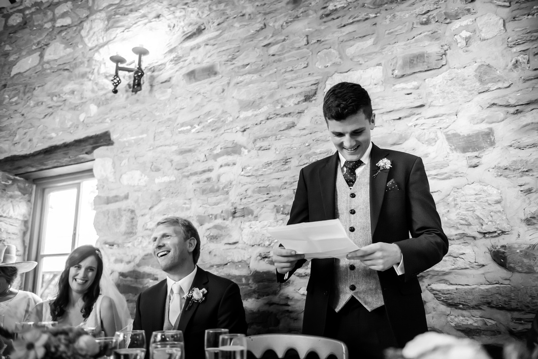 Black and white image of the best man giving his speech at a wedding at Plas Isaf.