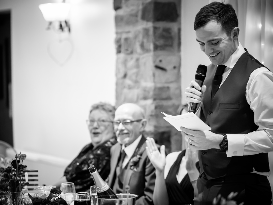 Black and white image of the groom giving his speech at his wedding at Beeston Manor.