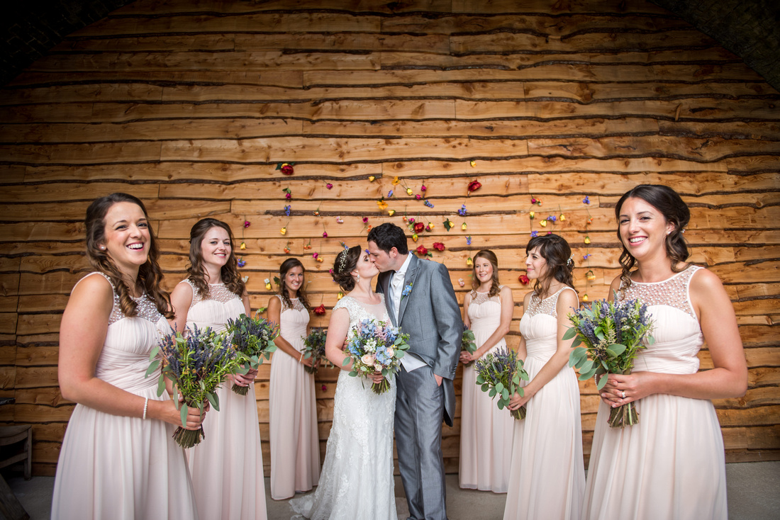 Image of the bride and groom sharing a kiss in between all of their bridesmaids at Tower Hill Barns.