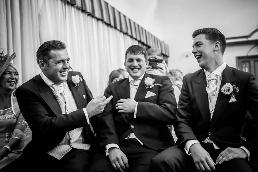 Black and White image of the groom and his ushers having a laugh before the wedding ceremony at The Kinmel