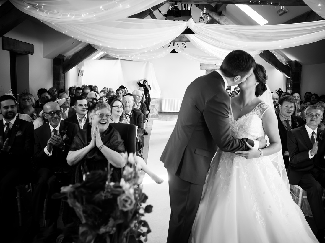 Black and white image of the bride and groom's first kiss as a married couple at a wedding in Lancashire at Beeston Manor.