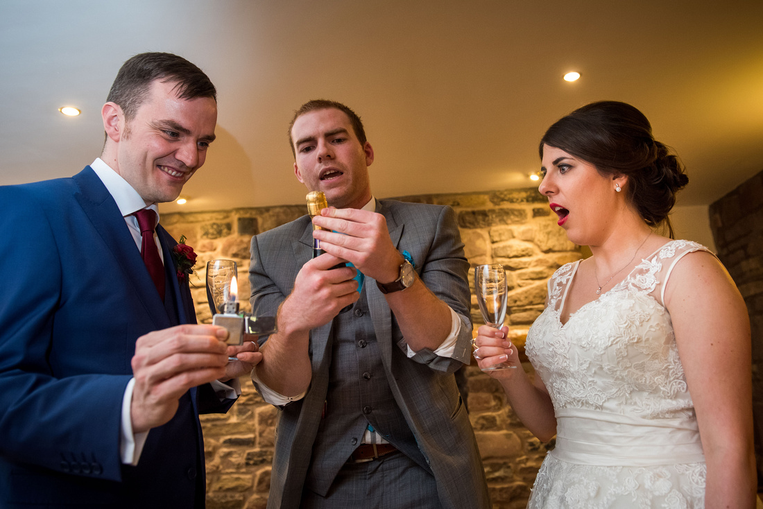 Photo of the bride and groom enjoying a magician's tricks at their wedding at Beeston Manor.