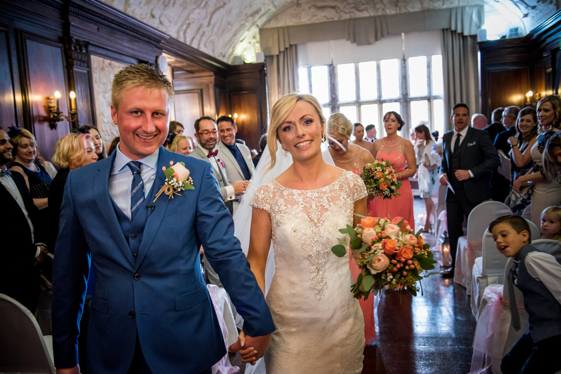 Image of the bride and groom leaving their wedding ceremony as a married couple. Wedding in Portmeirion.