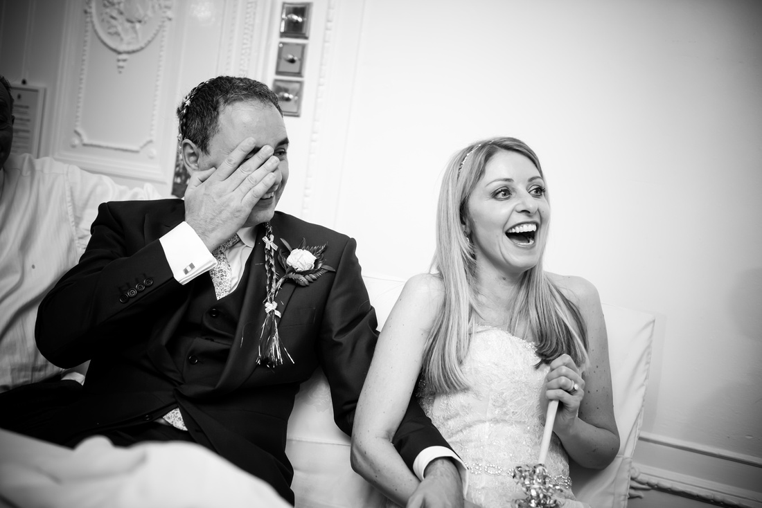 Black and white image of the bride and groom laughing during the speeches at their wedding at Taplow House, Buckinghamshire.