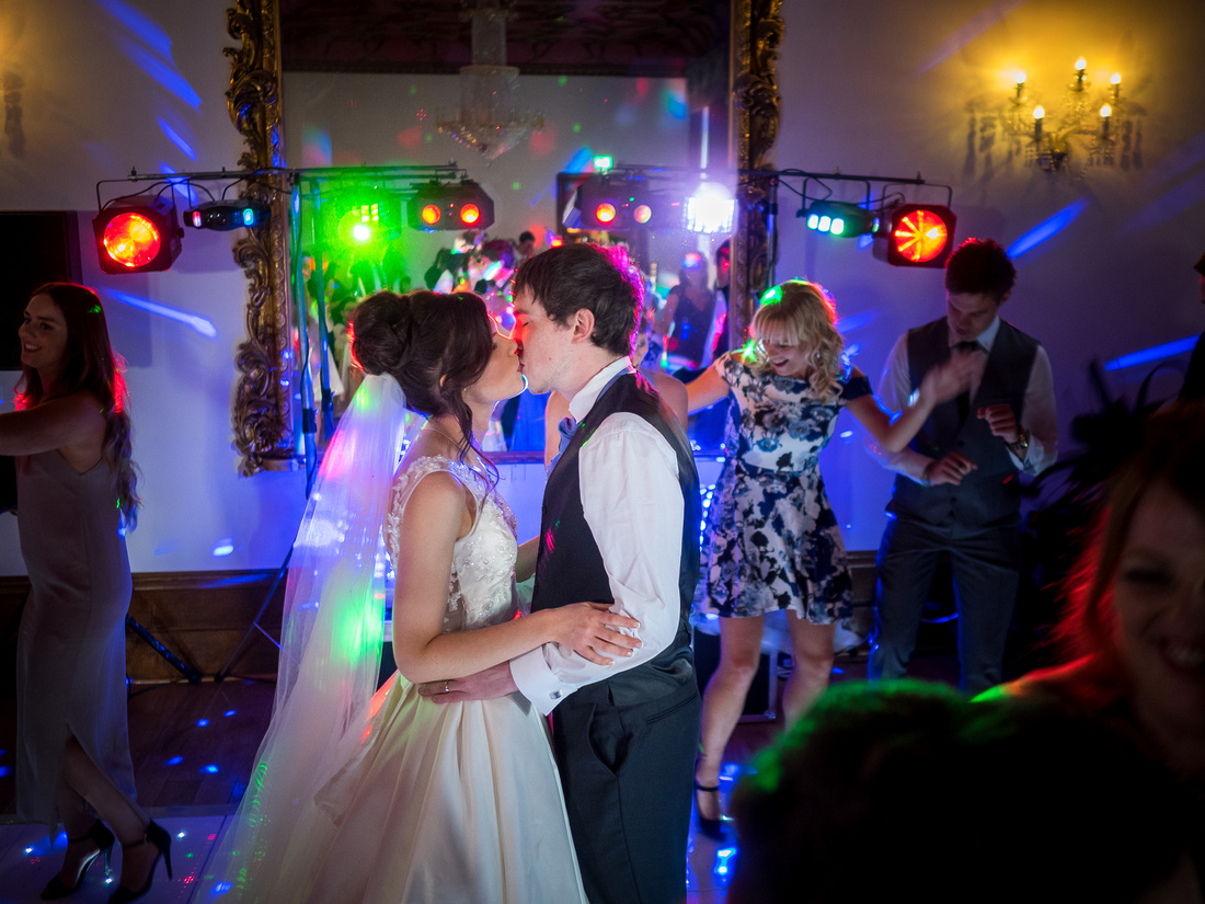Photo of the bride and groom sharing a kiss on the dance floor at a wedding at Ruthin Castle.